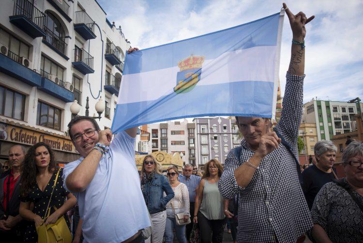 Dos ciudadanos portan una bandera de La Línea. Marcos Moreno