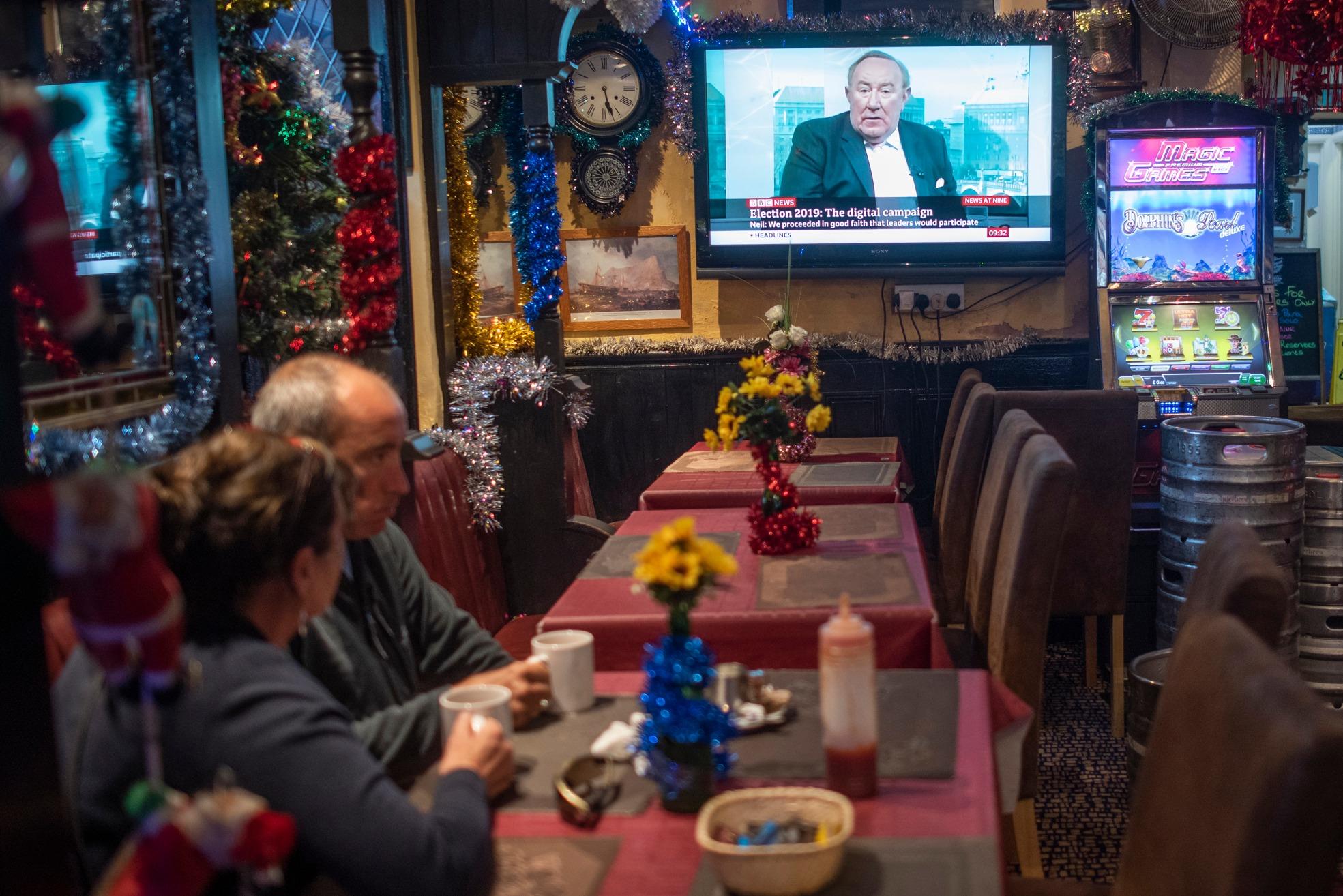Varias personas siguen las noticias en un bar. Marcos Moreno